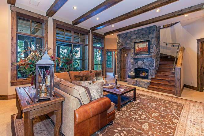 Spacious Family Room featuring a stone fireplace and access to hot tub deck | Northstar Luxury Home