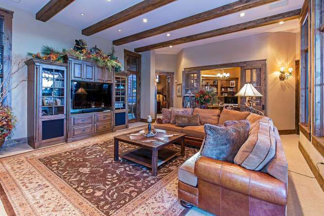 Spacious Family Room featuring a stone fireplace and access to hot tub deck | Tahoe Ski Resort Real Estate