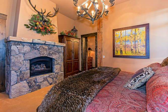 Guest Bedroom with en suite bathroom and stone fireplace   Lake Tahoe Real Estate