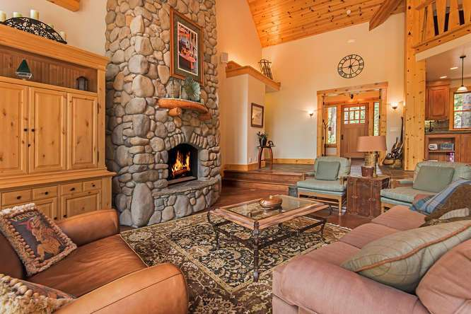 Grand Living Room with Vaulted Ceilings and Floor to Ceiling Stone Fireplace