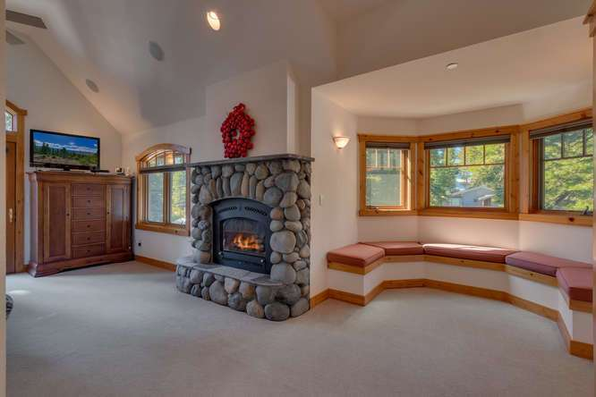 Breathtaking Master bedroom with rock fireplace