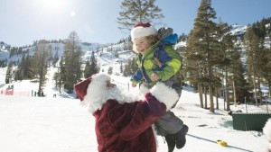 Image of Santa with little girls playing in the snow at Holidays at Squaw Valley | Alpine Meadows for How to Spend the Holidays in North Lake Tahoe blog post