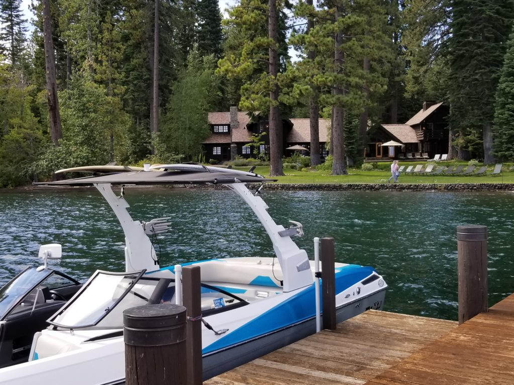Tahoe Lakefront Real Estate | image of boat on pier with home nestled in the trees on Lake Tahoe for Lake Tahoe Lakefront Real Estate page